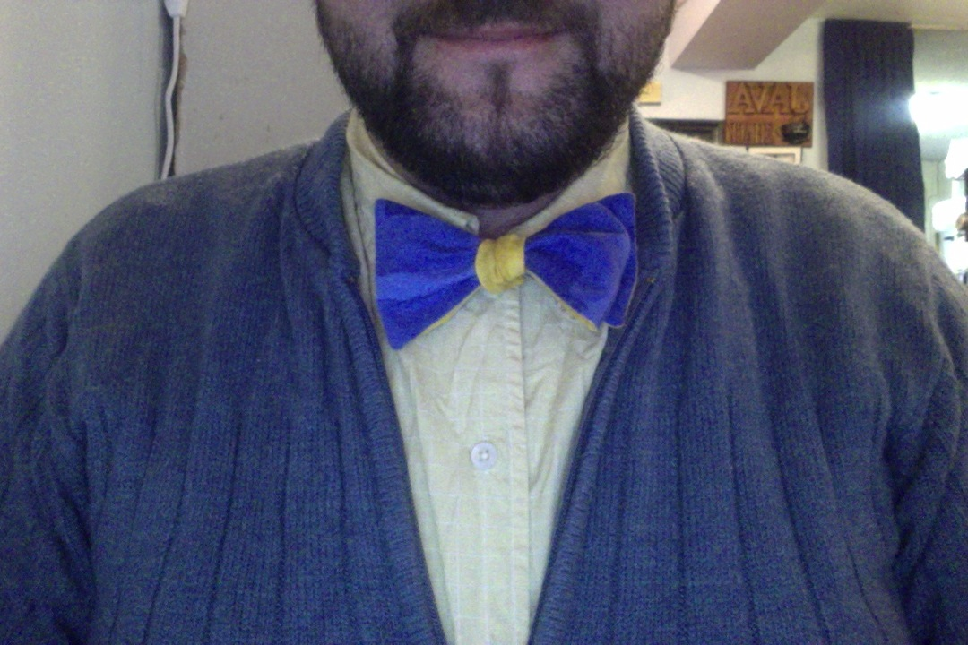 Blue and Gold double sided bow tie tied blue across, gold in the center on a gold shirt with a blue sweater