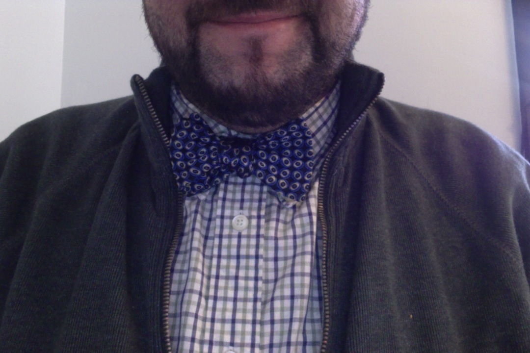 Blue with black bow tie on white with blue/green shirt and a green sweater.