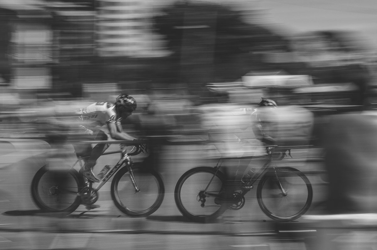 blurry photo of two bicyclists racing
